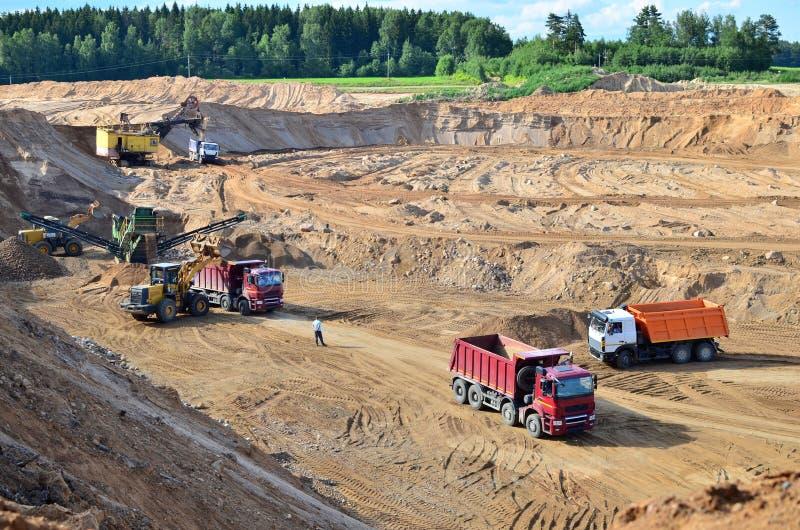 Ładowarka z przodu koła ładuje piasek do samochodu samowyładowczego Maszyny ciężkie w kopalniach, koparkach i samochodach ciężaro zdjęcia royalty free