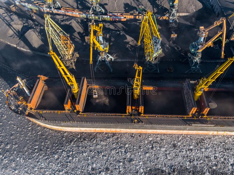 Ładowniczy coalmining w porcie na ładunku tankowa statku z dźwigowym wiadrem pociąg Powietrzny odg?rny widok zdjęcie stock