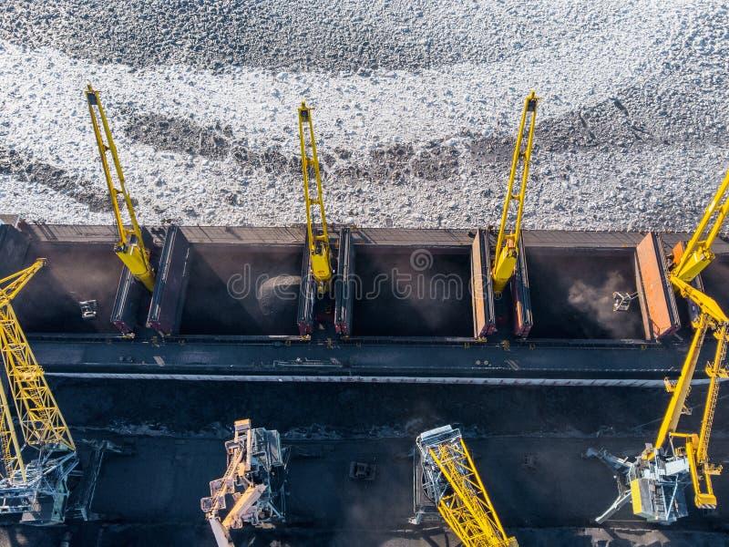 Ładowniczy coalmining w porcie na ładunku tankowa statku z dźwigowym wiadrem pociąg Powietrzny odg?rny widok fotografia stock