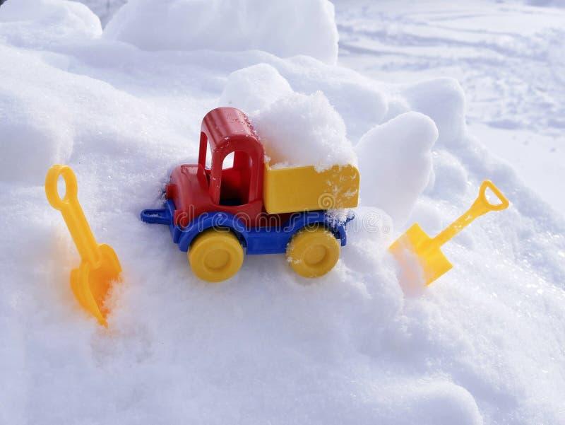 Ładująca jaskrawa klingeryt zabawki samochodu ciężarówka, dzieci ostrza w śniegu w naturalnym środowisku pojęcie zimna śnieżna wy fotografia royalty free
