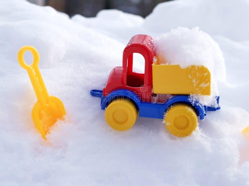 Ładująca jaskrawa klingeryt zabawki samochodu ciężarówka, dzieci ostrza w śniegu w naturalnym środowisku pojęcie zimna śnieżna wy zdjęcia stock