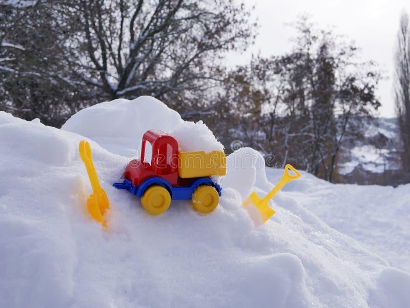 Ładująca jaskrawa klingeryt zabawki samochodu ciężarówka, dzieci ostrza w śniegu w naturalnym środowisku pojęcie zimna śnieżna wy zdjęcie royalty free