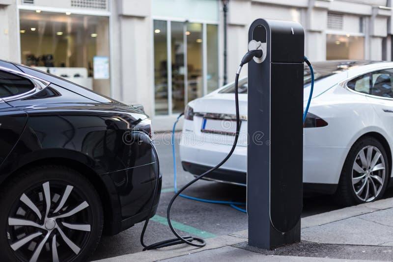 Ładuje nowożytny elektryczny samochód na ulicie jako przyszłość automobilowy przemysł zdjęcie stock