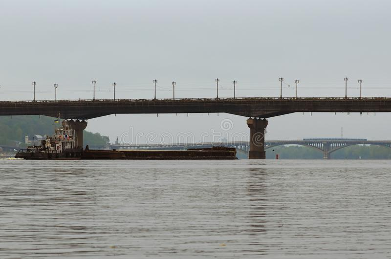 Ładunek dostawa rzecznym transportem Holownik łódź holuje barki z piaskiem Paton most i metro most w tle zdjęcia royalty free