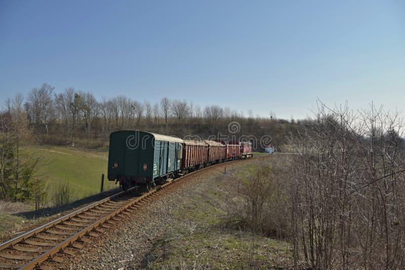 Ładunku pociąg Pociąg towarowy przechodzi przez wiosny wsi Budowa kolejowi ślada Kolejowa infrastruktura obraz royalty free