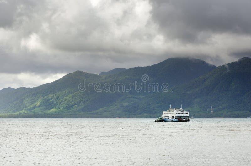 Ładunku prom w tropikalnym morzu pod monsun burzy ciężkimi chmurami i tropikalnej Koh Chang wyspie na horyzoncie w Tajlandia fotografia royalty free