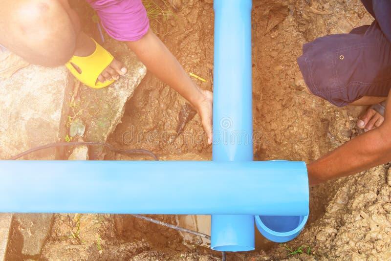 Łamana drymba w dziurze z wodnym ruchem przy pobocza i hydraulika działania naprawą zdjęcia stock