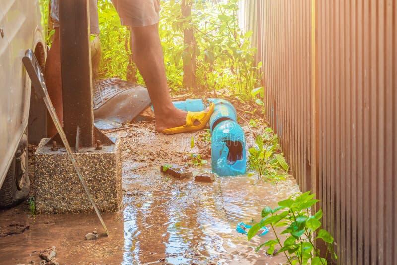 Łamana drymba w dziurze z wodnym ruchem przy pobocza i hydraulika działania naprawą zdjęcie stock