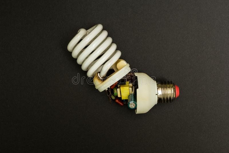 Łamana fluorescencyjna lampa na czarnym tle obraz stock