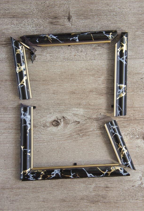 Łamana fotografii rama na drewnianym tle fotografia stock