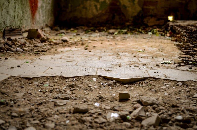 Łamana podłoga z krakingowymi płytkami w przegranym abandonend budynku obraz royalty free