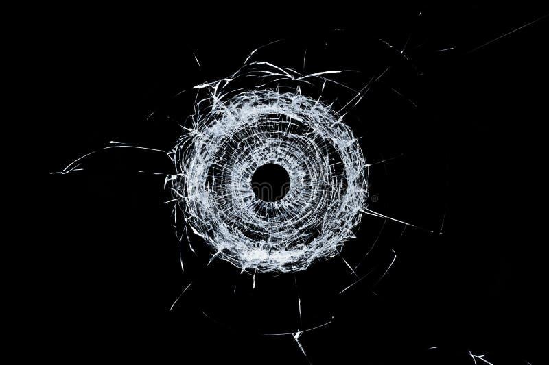 Łamanego szkła pojedynczy dziura po kuli w szkle odizolowywającym na czerni zdjęcie stock