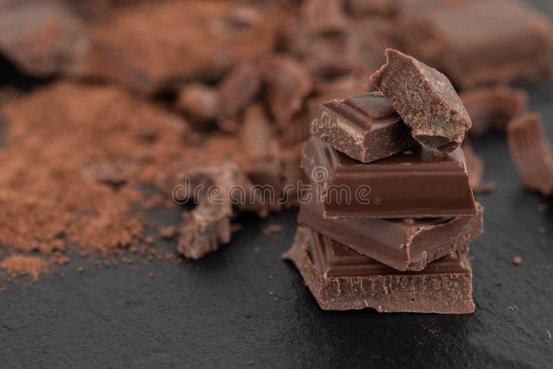 Łamani czekolada kawałki i kakaowy proszek na ciemnym tle obrazy stock