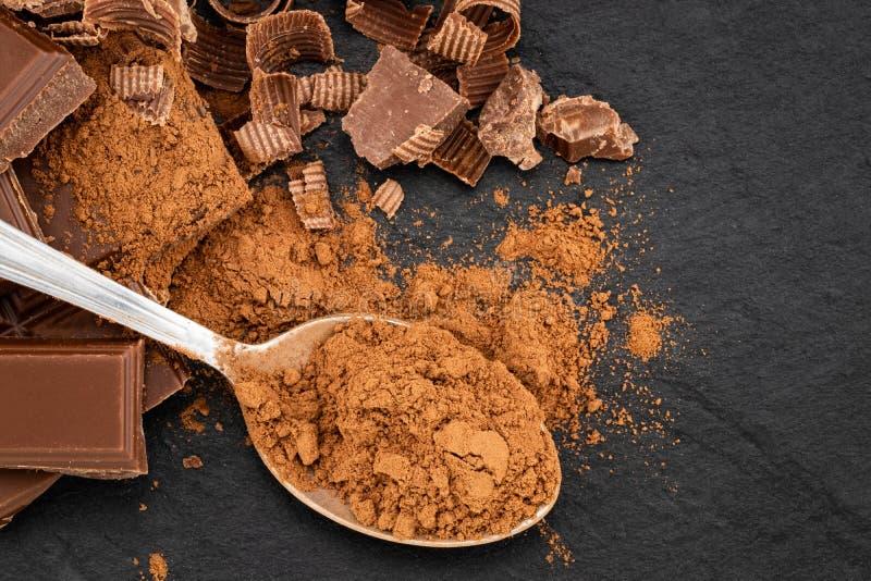 Łamani czekolada kawałki i kakaowy proszek na ciemnym tle zdjęcia royalty free