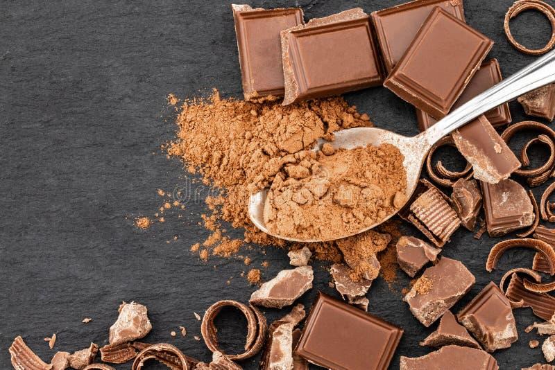 Łamani czekolada kawałki i kakaowy proszek na ciemnym tle obraz royalty free