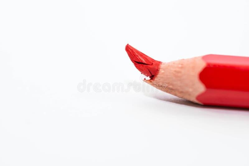 Łamany czerwony ołówek na ostrości zakończeniu w górę makro- strzału odizolowywającego na białym tle obraz stock
