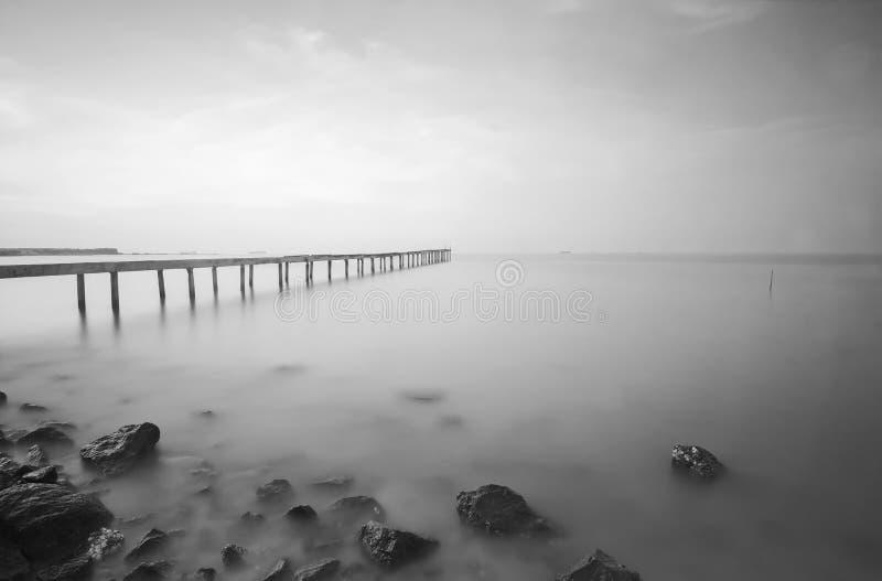 Łamany drewno most, fala rozbija na morzu w czarny i biały i obraz stock
