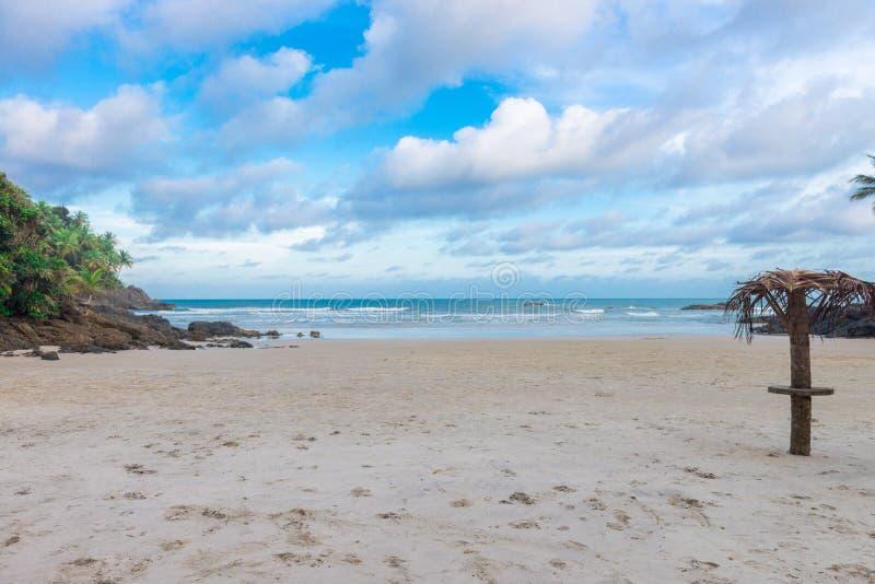 Łamany parasol przy skalistej plaży popołudniem zdjęcia stock