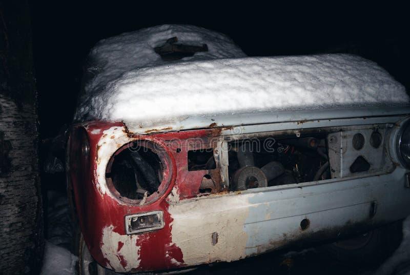 Łamany stary samochód zakrywający z śniegiem przy nocą zdjęcie royalty free