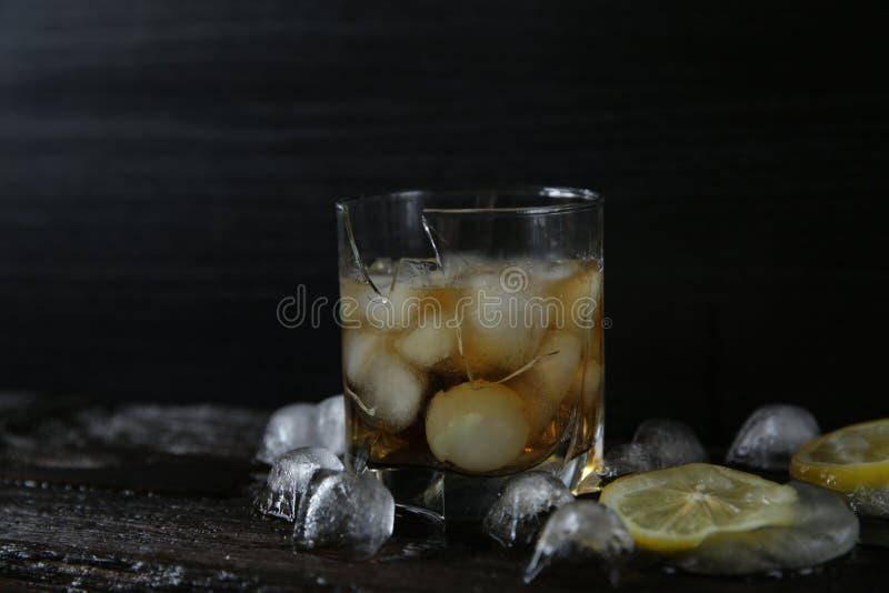 ?amany szk?o whisky z lodem na drewnianym czarnym tle fotografia royalty free