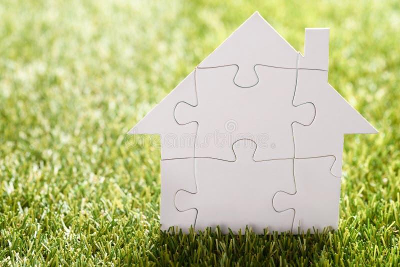 Łamigłówka dom na trawie obraz stock