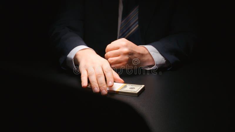ŁAPÓWKA: Biznesmen bierze pieniądze plika od stołu przy negocjacja czasu dolarem amerykańskim fotografia stock