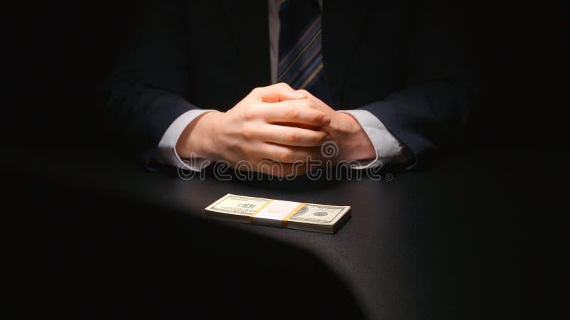 ŁAPÓWKA: Biznesmen czeka pieniądze na stołowym dolarze amerykańskim i stawia - dwa osoba obrazy stock