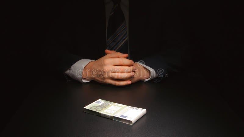 ŁAPÓWKA: Biznesmen czeka pieniądze na stołowym euro i stawia - Dwa osoba obrazy stock