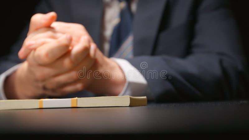 Łapówka: Biznesmen i pieniądze wiążemy na stole przy negocjaci czas chujący krzywka zdjęcie royalty free