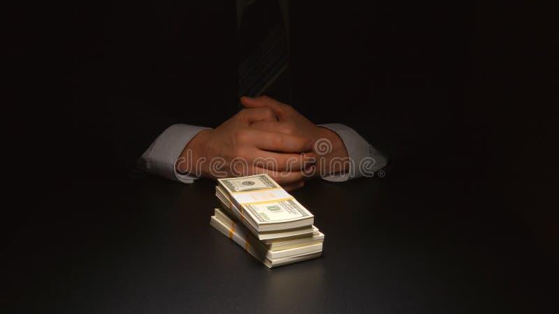 ŁAPÓWKA: Biznesmen siedzi blisko rozsypisko pieniądze na stole zdjęcie stock