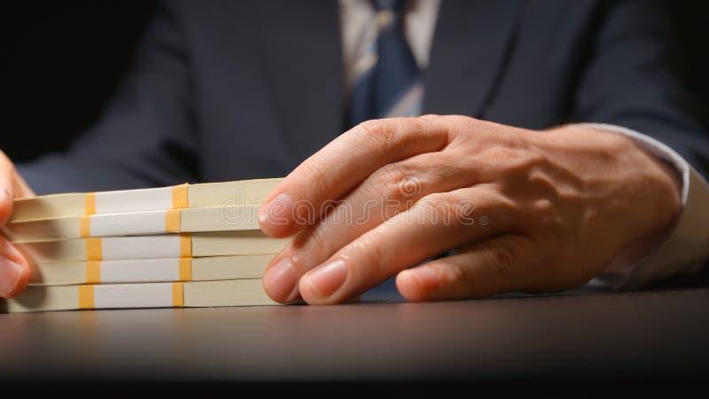 ŁAPÓWKA: Biznesmen trzyma pieniądze plika przy rękami na stołowy chujący krzywka obraz stock