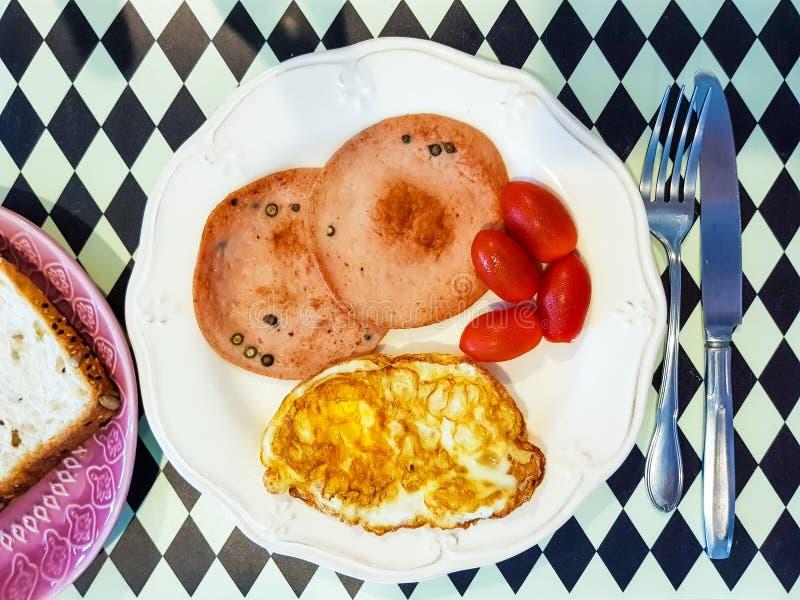 Łatwy amerykański śniadanie wliczając gotującego smażącego jajka, pieprzowej wieprzowiny kiełbasy, czerwonego pomidoru i piec na  zdjęcie royalty free