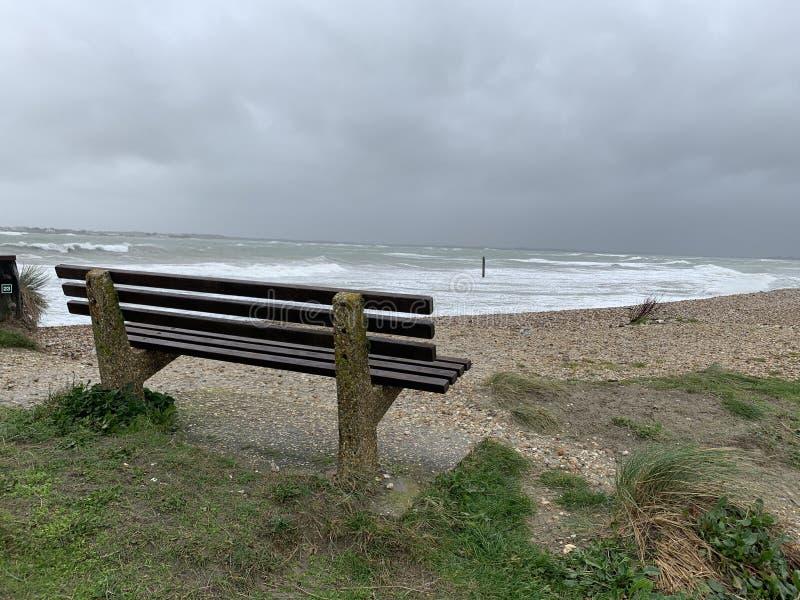 Ławka na plaży w ciemny, pochmurny dzień obraz royalty free