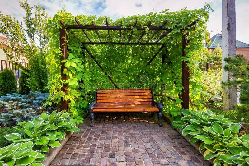 Ławka w dom kształtującym teren ogródzie zdjęcia stock