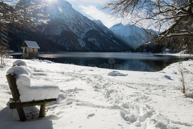 Ławka zakrywająca z śnieżną koc scenicznym przełęczem Jezioro Lago Del Predil w zimy scenerii, Italy zdjęcia stock