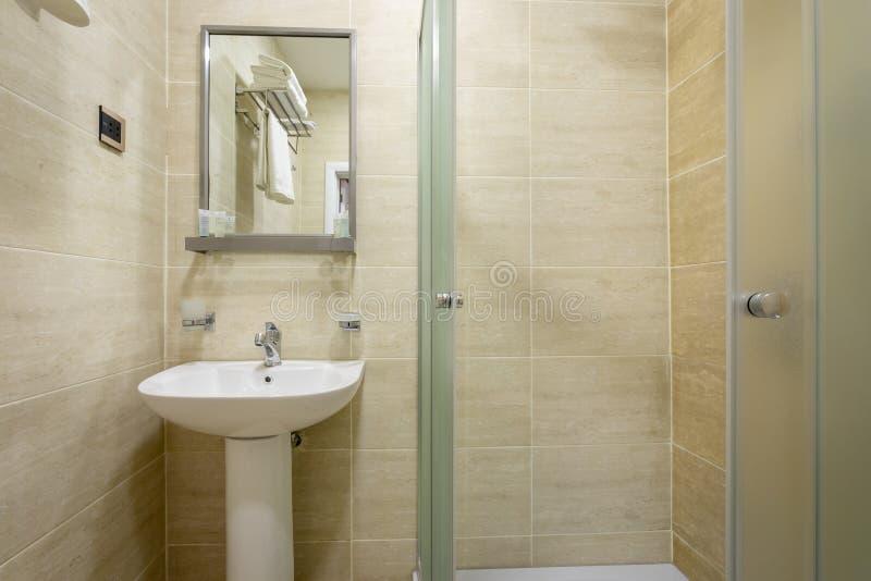 Łazienka, płytki i jaskrawi kolory miotła, prysznic z oszroniejącymi drzwiami, lustro nad zlew Wieszać ręcznika nad toaletą na h obraz royalty free