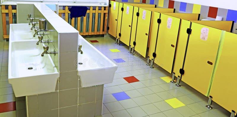 Łazienka pepiniera z biel zlew i żółtymi toaletowymi drzwiami obraz stock