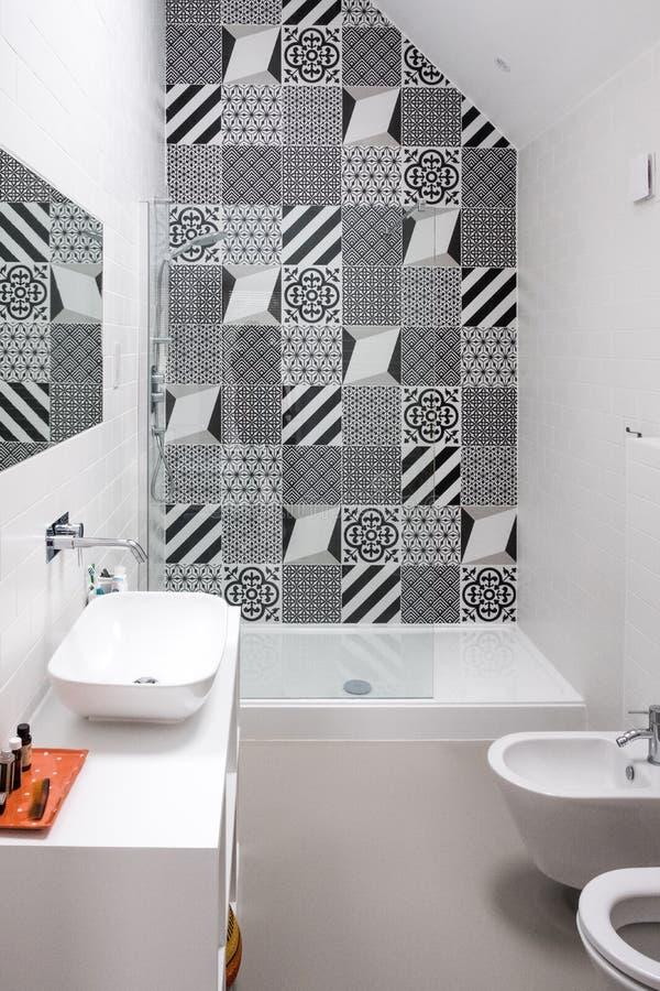 Łazienka z prysznic jednostki, toalety, bideta i basenu jednostką z czarny i biały monochromatycznymi patchwork płytkami i wysoki obrazy stock