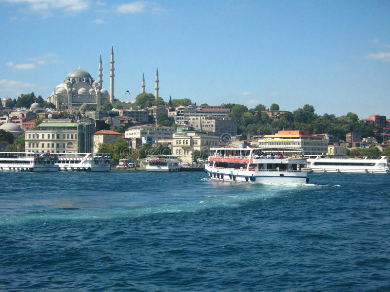 Łodzi crossiog Bosphorus w mieście Istanbuł, Turcja i meczet z wysokimi minaretami na tle, obrazy royalty free