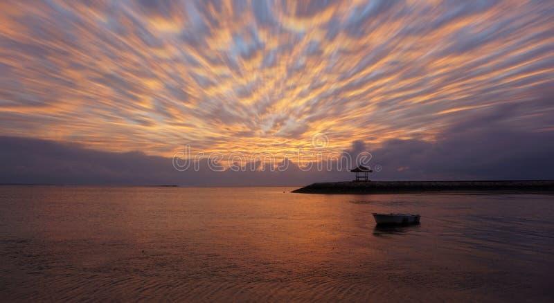 Łodzi rybackiej sylwetka unosi się na morzu z gnaniem chmurnieje w nieba tle obraz stock