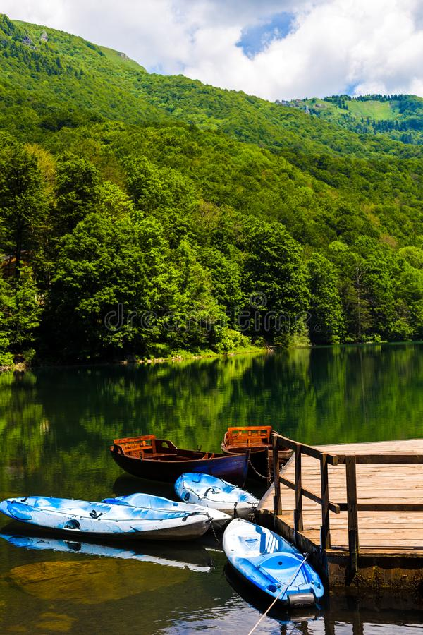 Łodzie blisko brzeg jeziorny, piękny odbicie w wodzie drzewa, Czarny jezioro w Durmitor parku narodowym w Zabljak, obrazy royalty free