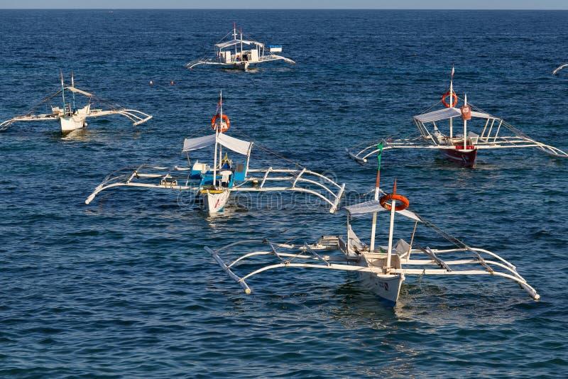 Łodzie czeka turystów w wodzie morskiej podróżować między wyspami Wyspa Panglao, Filipiny obrazy stock