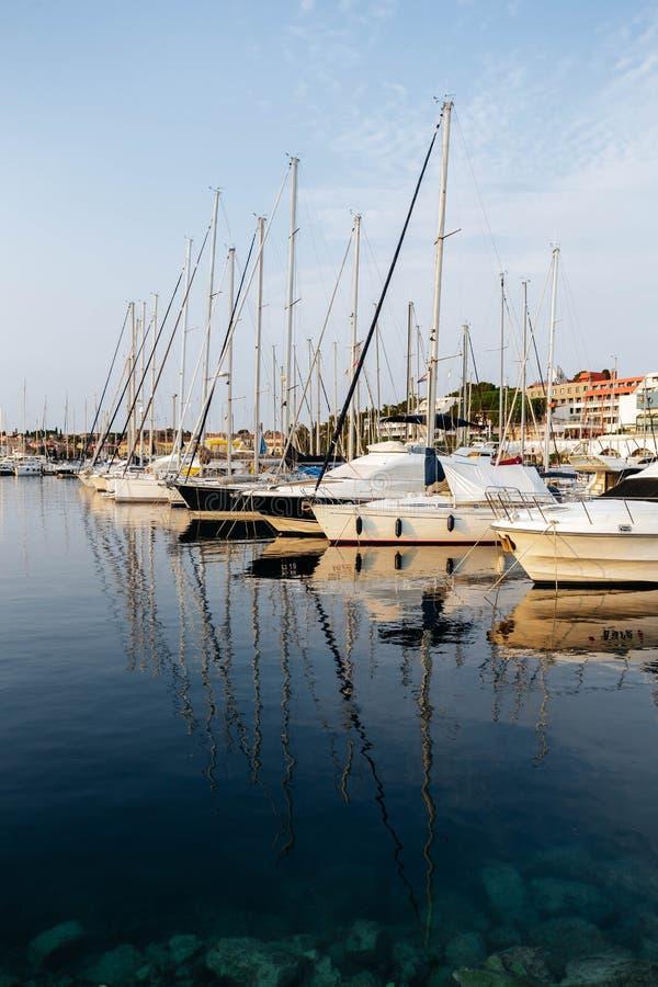 Łodzie i statki przy molem w Rovinj, Chorwacja przy zmierzchem Maszty odbijają w morzu obraz stock