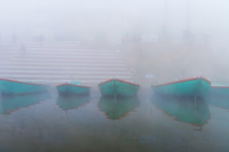 Łodzie na świętym rzecznym Ganges przy zimnym mgłowym zima rankiem varanasi zdjęcie stock