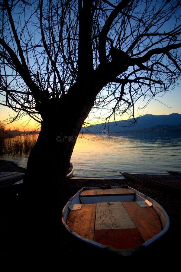 Łodzie na brzeg jezioro przy zmierzchem zdjęcie royalty free