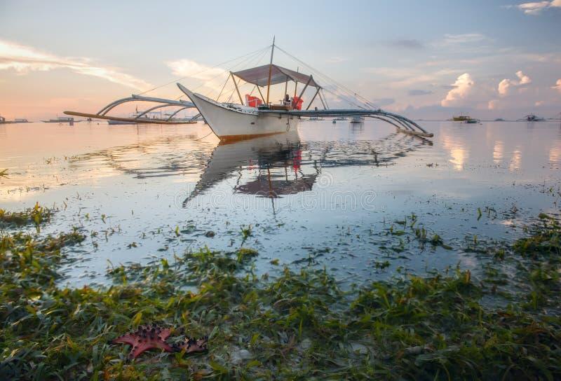 Łodzie na tropikalnej plaży przy wschodem słońca fotografia stock