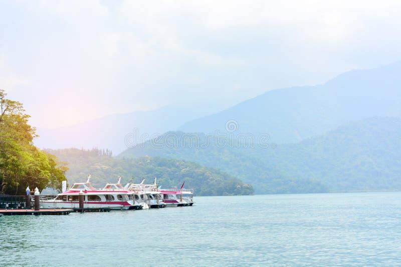 Łodzie podróżne parkują na molo z zachodem słońca i górskim tłem krajobrazowym, jeziorem księżycowym, Tajwanem zdjęcie stock