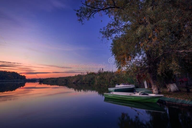 Łodzie rybackie przy pontonem na jeziorze w wieczór obraz stock