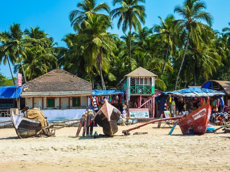 Łodzie rybackie, tropikalni drzewka palmowe, bungalowy i uliczny życie w Palolem, wyrzucać na brzeg zdjęcie stock