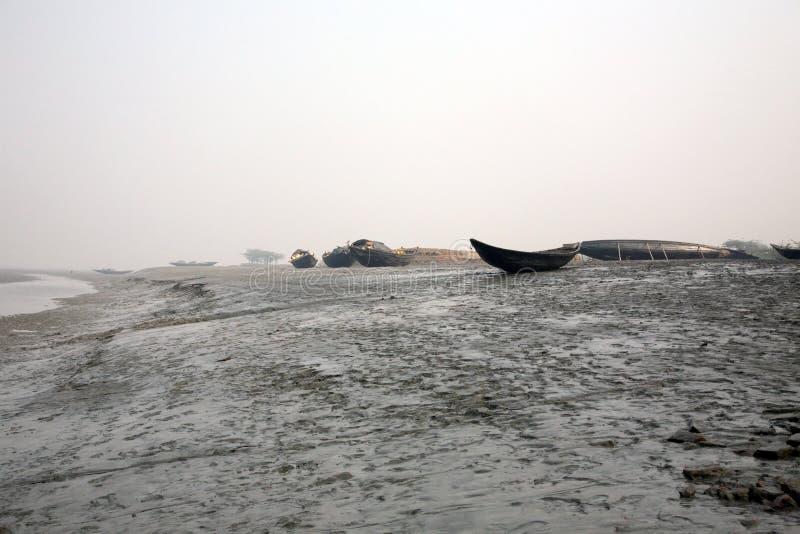 Łodzie rybacy splatali w błocie przy niskim przypływem na rzecznym Malta pobliskim Konserwuje miasteczku, India obrazy royalty free
